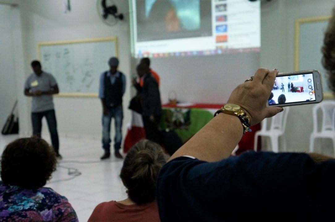 Participante do Seminário das Pastorais Sociais de SC registra esquete de haitianos que conta a história de família enganada por coiote, que fica com todo o dinheiro deles. (Foto: Marcelo Luiz Zapelini/Agência Sul 4)