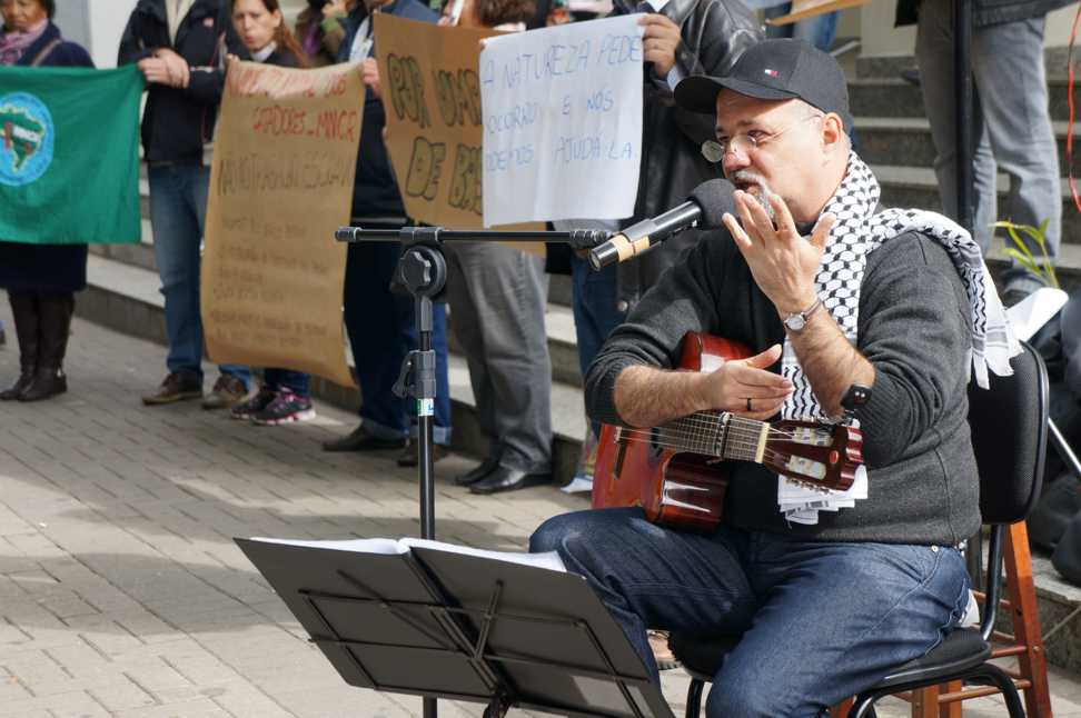 """Em ato público, o cantor popular Pedro Munhoz declama poema: """"é preciso questionar quem pilota a economia"""". (Marcelo Luiz Zapelini/Agência Sul 4)"""